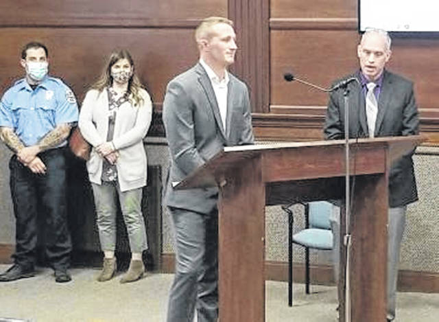 Sidney's newest firefighter Jacob Finfrock, left, and his wife Katie, look on as Sidney's newest police officer Hayden Bronne, center, is introduced to Sidney City Council Monday, April 12, by Police Chief Will Balling, right, immediately before he is sworn-in. Finfrock and Broone were both introduced to council members during the evening meeting.
