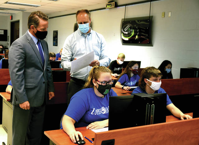 Ohio Lt. Governor Jon Husted chats with instructor Jeremy Kettering as his Pre-Engineering students, Gracie Russell of Anna, and Jacob Yinger of Jackson Center, work on their classroom computers on Tuesday morning.