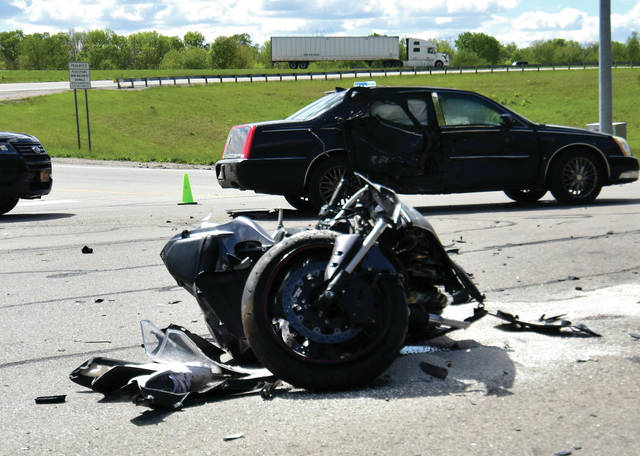 A motorcycle and a car sit in the middle of the intersection of County Road 25A at the southbound 83 exit ramp off I-75 (Farrington Road interchange) in between Troy and Piqua following a crash that left the motorcycle driver dead on Wednesday afternoon, May 12.