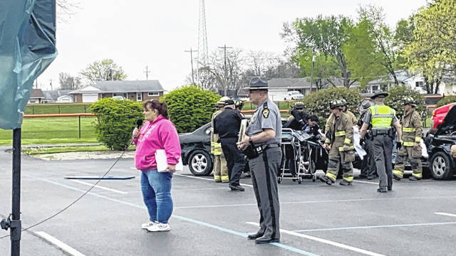 Event speaker Laura Cruea, in pink, with Ohio State Highway Patrol Lt. Joseph Gebhart, right, looking on, addresses Jackson Center students on the dangers of being involved in an alcohol or distracted driving related crash. Jackson Center Police and Jackson Center Schools teamed up to hold its triennial mock crash on April 28.