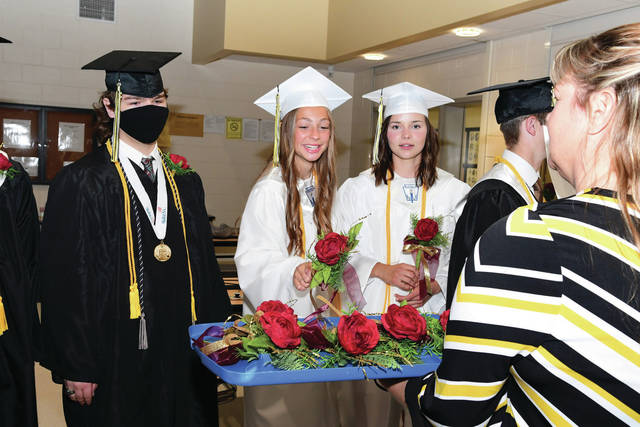 Seniors Makenna Maurer and Emma Koenig select their flowers for the processional during the 2021 Botkins High School graduation ceremony on Sunday, May 23.