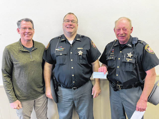 Community Connection Fund Trustee John Morreale presents the Auglaize County Sheriff's Auxiliary with a $1,500 check to purchase external bulletproof vest carriers. Pictured, left to right, are Morreale, Auglaize County Sheriff Michael Vorhees and Auxiliary Deputy Randy Baber.