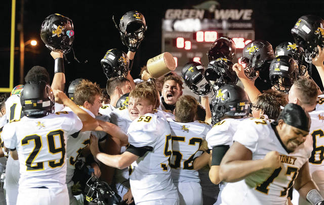 Sidney players celebrate with the Little Brown Jug after beating Greenville 56-0 in a Miami Valley League game on Aug. 28, 2020 at Harmon Field in Greenville. The teams will meet in Week 3 this year after the matchup had traditionally been scheduled for Week 10. The squads played in Week 1 last year due to the Miami Valley League moving up traditional rivalry matchups to the start of the season in case COVID-19 outbreaks later in the year forced cancellations.