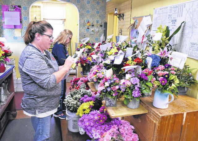Lisa Heaton, front, of Minster, checks the delivery list for flower bouquets while Sherry Moran, of Sidney, inspects and helps create the arrangements at Dekker's Flower Shop in Sidney. Mother's Day is one of the busiest time of year for all of the local flower shops. Heaton is an employee of Dekker's Flower Shop while Moran enjoys volunteering her time for this holiday.