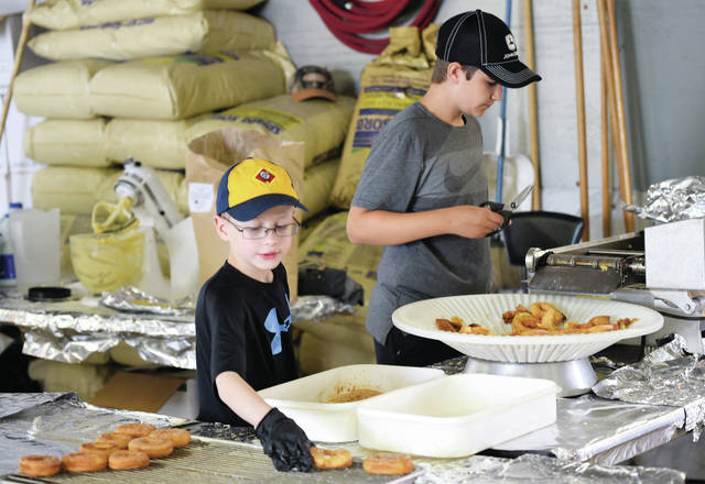 Sean Wren, right, and Luke Schmerge, both of Jackson Center from Boy Scout and Cub Scout Troop 98, prepare doughnuts during the 2019 Jackson Center Community Days festival. Sean is the son of Brad and Bev Wren. Luke is the son of Paul and Karen Schmerge.