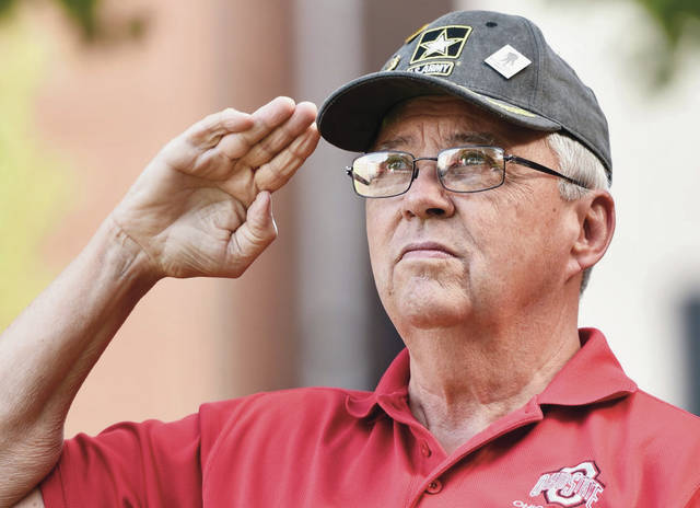 Army 1965-71 Ted Hook, of Sidney, salutes the U.S. flag during the singing of the National Anthem by Fairlawn High School Sophomore Caroline Scott on the courtsquare Monday, May 27, 2019. Memorial Day services were held on the courtsquare and then at Graceland Cemetery.