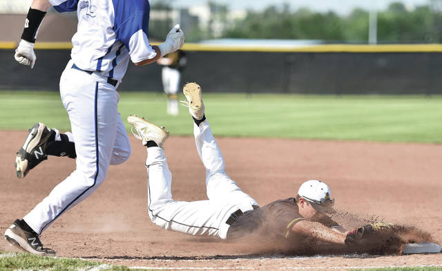 Sidney's Carson Taylor dives into first to force out Miamisburg's  Teagan Williams at Miamisburg on Thursday.
