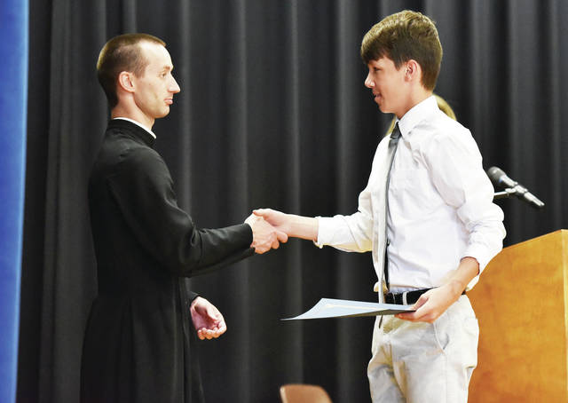 Jeremiah LaForme, right, gets his diploma and a handshake from the Rev. Jarred Kohn during the Holy Angels eighth grade graduation ceremony on Tuesday, May 25.