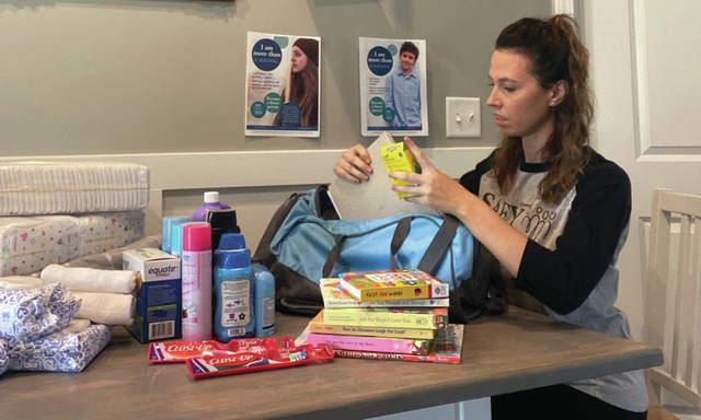 Sylvia Roop, foster parent recruiter for SAFY, stuffs duffel bags full of necessities to be given to foster youth when they are placed in a foster home.