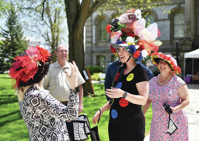 Kelly Edwards, left, front, of Anna, reacts to the elaborate hat worn by her friend since high school, Jackie Verhotz, of Sidney, during the Kentucky Derby Affair on the Square event. Watching them are Nick and Melinda Watercuter, left to right, back, of Sidney. The event was held on Saturday, May 1. Guests could play garden games, enter a raffle and eat hors d'oeuvres.