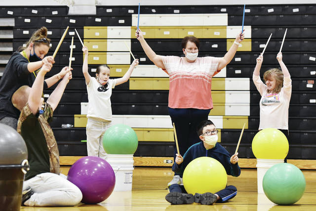 Taking part in some drumming cardio at Sidney High School are, left to right, Sidney High School Paraprofessional Peggy Bean, Kaleb Terry, 16, son of Sean and Mindy Terry, Audrea Litton, 16, daughter of Jeff Litton and Amy Matthieu, Sidney High School Paraprofessional Michelle Hammer, Jacob Martin, 16, son of Becky and Tom Martin, and Abby Adams, 17, all of Sidney, daughter of Dee and Mike Adams. The drumming cardio class was led by Sidney-Shelby County YMCA employee Jodi Cantrell and held on Wednesday, May 12. The Sidney-Shelby County YMCA has been coming once a month to hold yoga classes for the multiple disabilities class at Sidney High School but changed it up this time with cardio drumming.