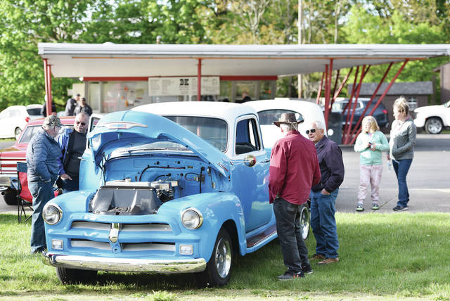 Looking over a bright blue 1954 Chevy are, left to right, Dan Ryan, of Port Jefferson, Larry Wogaman, of Houston, Rusty Woodward, of Houston, and Don Ike, of Sidney. The Chevy was one of the classic cars on display during a car show at the BK Root Beer Stand on Tuesday, May 11.