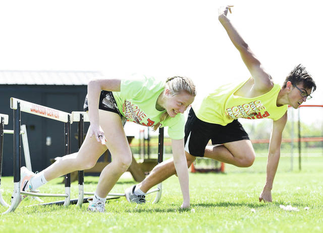 Addie Biederman, left, 14, of Jackson Center, daughter of Laura and Jr Biederman, races with Noah Rains, 17, of Anna, son of Berry and Karen Rains, through an obstacle course that was one of the many activities held during Field Day at Jackson Center Local Schools on Friday, May 14. Activities included a home run derby, scavenger hunt and capture the flag. Students also ate hamburgers grilled in the courtyard.