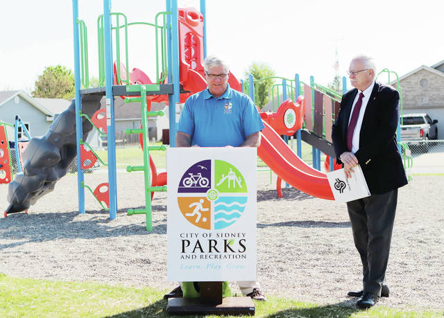 City of Sidney Parks and Recreation Director Duane Gaier, left, speaks as Mayor Mike Barhorst listens during a ribbon cutting ceremony for Heritage Manor Park on Saturday, May 15. The new park is located at 2440 Apache Dr..