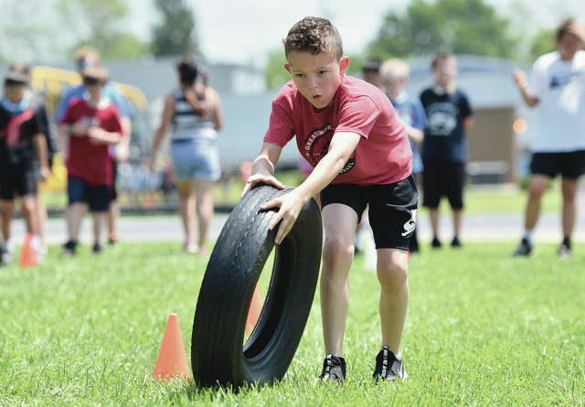 Carson Fryman, 10, of Sidney, son of Jasmine Bird and Devin Fryman, pushes a tire around cones during a group race at Northwood Intermediate School on Thursday, May 20. The tire race was one of many activities students participated in for Field Day. Field Day is an annual end of the year event for students.
