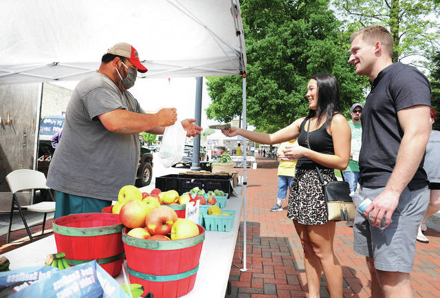 Ken Bergman, left to right, of Russia, sells brussels sprouts to Gloria Dicke, of Sidney, and Nick Gerschutz, of Columbus, at The Great Sidney Farmer's Market's 2020 season opening day.