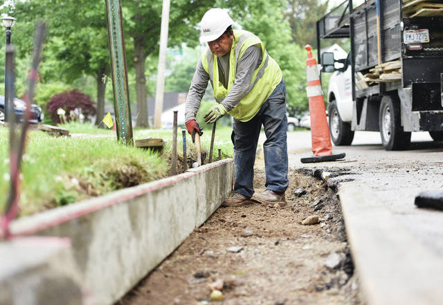 Adan De Latorre, of Union City, works on replacing a gutter curve on Johnston Drive in the rain on Wednesday, May 26. De Latorre said they are doing repair work on several streets in Sidney.