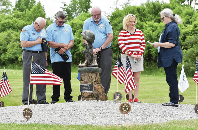 Vice Mayor Mardi Milligan, far right, says a prayer, on Thursday, May 27, at the new veterans memorial placed near the entrance to the Sidney Veterans Center. Listening to Milligan are, left to right, Sidney American Legion First Vice Commander Rick Lunsford, of Sidney, Head Trustee Jack Curl, of Houston, Post 217 Commander Jim Moorman, and Gallery 210 owner Mila Hamilton, both of Sidney. Hamilton painted the statue in memory of her dad, David Duning. Duning was a WWII Army Air Force veteran that was stationed in Normandy. The new memorial honors veterans of all wars and all branches of the U.S. military. The memorial is also meant to remind people of the service men and women that are prisoners of war and missing in action.