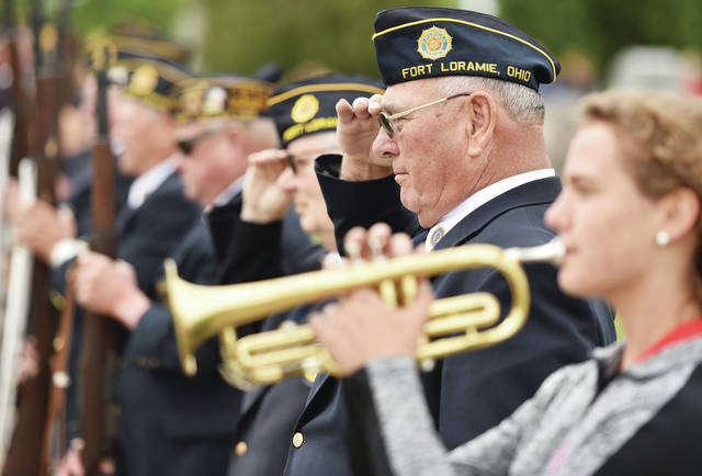 Fort Loramie American Legion Post 355 member Ken Meyer salutes while Cara Meyer, 17, both of Fort Loramie, plays Taps during a Memorial Day service at Houston Cemetery on Sunday, May 30. Rev. Kris Geise spoke during the ceremony. Cara is the daughter of Mark and Lynn Meyer.