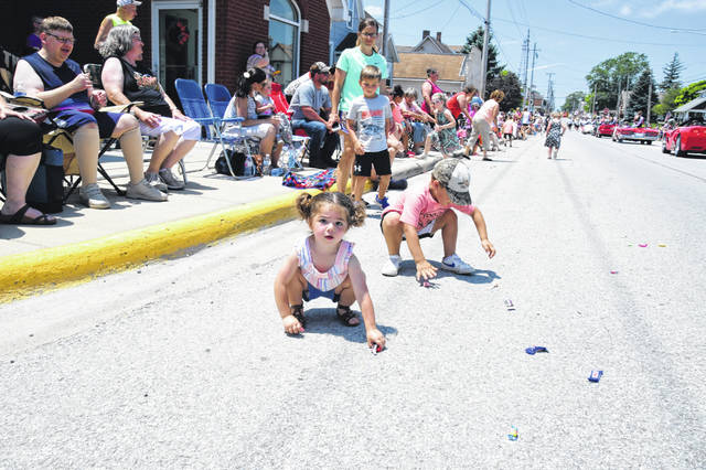 Tinley Brown goes after some candy during the Botkins Carousel Parade Sunday afternoon.. Tinley is the 2-year-old daughter of Tiffany and Thomas Brown, of Anna.