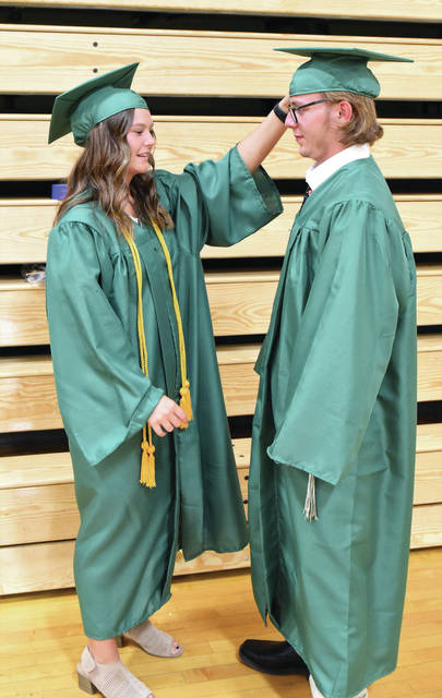 Macy Egbert, left, adjusts the mortarboard of David Burden before the start of the 2021 Anna High School graduation ceremony on Sunday, May 30.