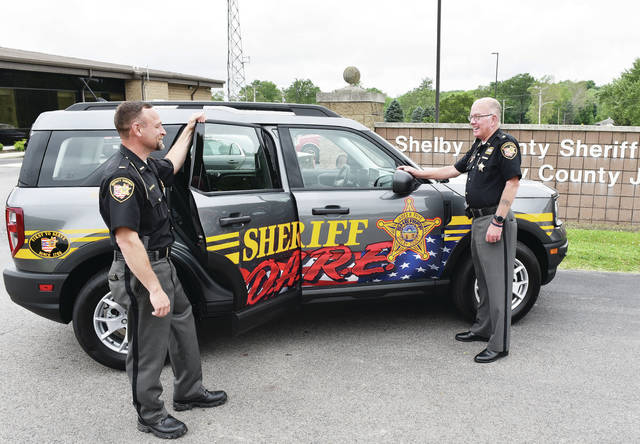 Lt. Jason Byers, left, and Shelby County Sheriff Jim Frye stand, on Wednesday, June 9, with the new Shelby County Sheriff's Office DARE vehicle.