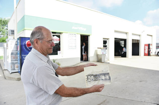 Tim Ernst shows a photo of what the gas station used to look like. Ernst added the garage to the current structure. In the doorway of Ernst Service Center is his wife and coworker, Sharon Ernst, on Thursday, June 10.