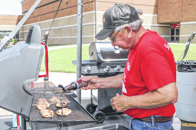 Gary Beaver cooks some pork loins from the Houston Congregational Church during Saturday's Houston Community Classics Festival.