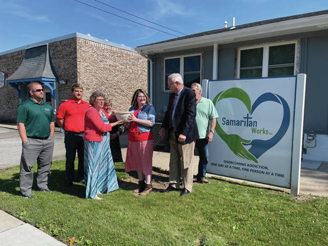 Standing, left to right, are Samaritan Works Board member Josh Ross, Board Member Ben Bowers, Executive Director Sheila Lundy, Board Member Eileen Hix, Outreach Coordinator/Office Manager Emily Roesser and Sidney Mayor Mike Barhorst, who is getting ready to draw the winning ticke.
