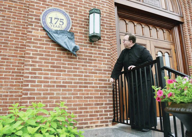 The Rev. Martin Fox unveils a new medallion mounted on the front of St. Remy Catholic Church on Wednesday, June 2. The medallion marks the 175th anniversary of St. Remy Parish which was started in 1846. The unveiling kicks off several months of activities. The next event will be a picnic after 11 a.m. Mass on Sunday, Aug. 22. A re-enactment of the founding of St. Remy Parish will be held at the picnic.