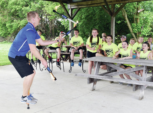 """Hardin-Houston Local School DARE. graduates watch as """"Crazy"""" Craig Muhlenkamp, of Minster, juggles fire and jumps on a pogo stick at the 9th annual Shelby County Sheriff's Office summer DARE Camp on Tuesday, June 8. This year 197 DARE graduates signed up, making this the largest group of campers yet. Students from Anna, Botkins, Jackson Center, Fairlawn, Fort Loramie, Russia, Christian Academy and Holy Angels Elementary are taking part in the camp. All involved students just finished the fifth grade. The campers learn about drug and alcohol prevention, water and watercraft safety, bicycle safety, good citizenship, good decision-making skills, and responsibilities. The camp was made possible by donations from several businesses throughout Shelby County."""