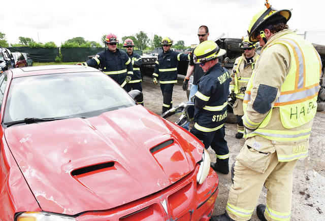 Sidney firefighter Josh Strawser, of Greenville, uses a brand new cordless spreader to pop open a car's hood during tool orientation at Wreckers Towing and Transport on Stolle Avenue. Older models of spreaders require thick cords that can get in the way during a rescue. Firefighters also practiced using a new ram, cutter and struts. Struts are used to secure vehicles to prevent them from moving or falling over. The ram can be used to push a dashboard up if it has been pushed down trapping someone. The cutter is like a super powered scissors that can cut through tough material. The orientation was done on Tuesday, June 8.