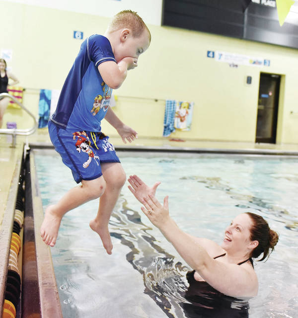 Lucas Watercutter, 5, jumps into the Sidney-YMCA swimming pool, with some help from his mom, Kelly Watercutter, both of Sidney, during the 6:30 p.m. parent and child Water Safety Week class on Wednesday, June 10. This is the 35th year of the annual water safety class for kids. Lucas is also the son of Ben Watercutter.