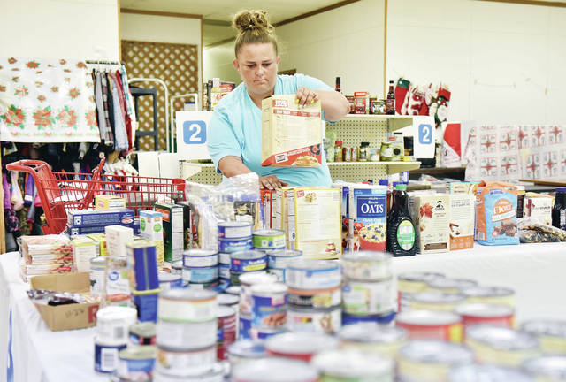 Jessica Satterwhite, of Sidney, grabs a box of pancake mix during the FISH of Shelby County's Grocery Giveaway on Friday, June 25. Winners of a raffle could pick-up the food at the FISH Christmas store. The food was donated by the Boy Scouts. The giveaway was organized by FISH volunteer Kathi Klauss.