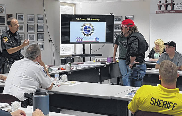 Darke County Sheriff Deputy Dan Stockslager, standing left, engages with SafeHaven Executive Director Doug Metcalfe, red hat, who is portraying a person experiencing a mental health crisis as other CIT Academy participants and instructors look on.