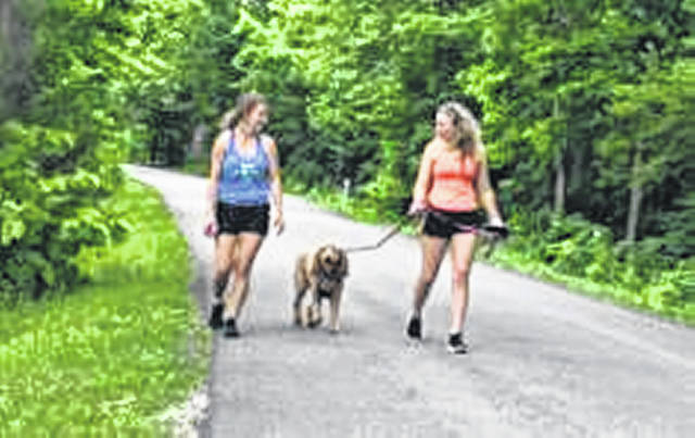 Mikayla Place, of Shawnee, left takes a walk in Tawawa Park Monday evening, June 21, with Danielle Schwartz, of Botkins, and her Zoey.