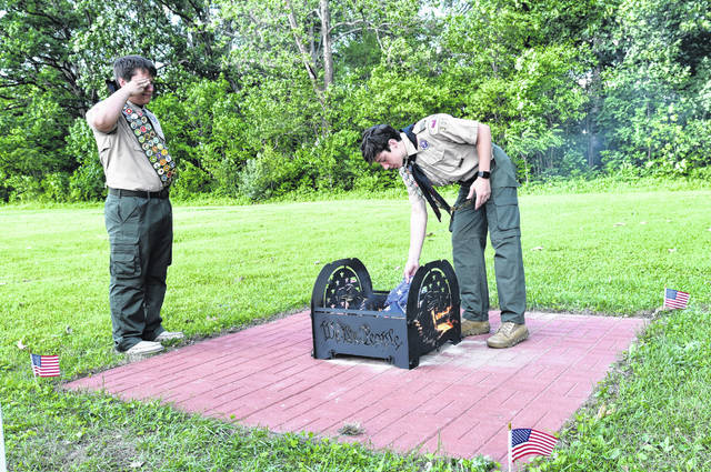 Aaron Simpson,16, places a worn flag in the fire pit that he constructed while Blaine Simpson, 16, stands at attention and salutes. Both Boy Scouts earned their Eagle Scout award with their projects.