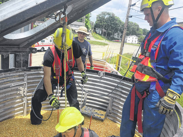 Sidney firefighters practice a grain rescue from a grain bin simulator Friday afternoon, June 18. Sidney Firefighter Jacob Lindsey, in the orange vest, uses probes to feel around inside of the bin containing dry, shelled corn while Sidney Firefighter Jordan Stemen waits to be rescued. Sidney Firefighter Jeff Simon, in the light blue jumpsuit inside of the bin, and Ohio Fire Academy instructor/Wauseon Fire Chief Rick Sluder looks on. The Ohio Fire Academy provided training for Shelby County fire departments in the classroom and on the Grain CART June 17-19.