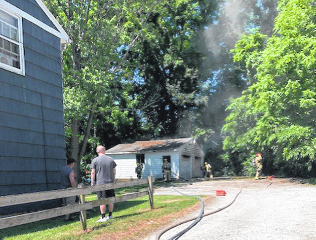 Sidney firefighters attack a garage fire seen with smoke coming from the structure at 841 N. Main Ave. Thursday morning, June 17.