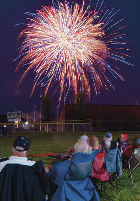 People watch the City of Sidney fireworks display from the comfort of lawn chairs near the Sidney Memorial Stadium on Sunday, July 4. The fireworks started at 10 p.m..