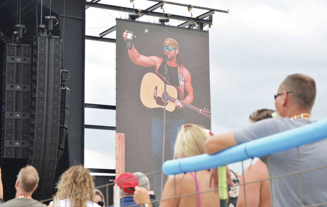Riley Green is displayed on one of the main stage side screes as he performs at Country Concert Friday, July 9.