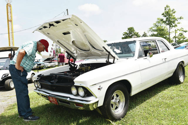 Lester Berning, of Sidney, looks under the hood of a 1966 Chevy Chevelle being shown by his neighbor, Craig Anderson in the Shelby County Fair's 24th annual cruise in on Sunday, July 25.