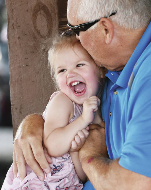 Madilyn Ward, left, 1, laughs as she gets a kiss from her grandpa, Greg Ward, both of Sidney, at the Shelby County Fair on Sunday, July 25. Madilyn is the daughter of Michael and Kristi Ward.