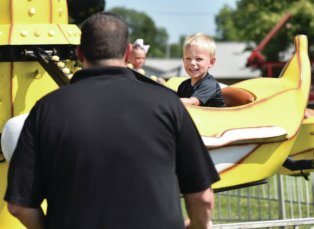 Calvin Scherge, 2, laughs at the hijinks of his dad, Josh Schmerge, both of Versailles, while riding a banana shaped plane at the Shelby County Fair on Monday, July 26. Calvin is also the son of Jamie Schmerge.