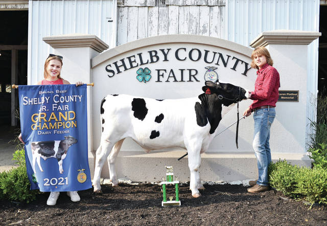 Anna Livestock 4-H Club member Zach Ambos, right, 17, of Sidney, son of Mike and Jennifer Ambos, won grand champion dairy feeder. Standing, left, is Michaela Ambos, 19.