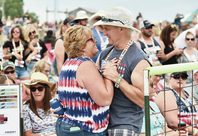 Chris, left, and Harold Long, of New Bremen, dance to Lorrie Morgan who was the first performer on the main stage at Country Concert on Friday, July 9.