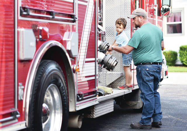 Sam Bower, left, 5, looks at a fire truck with his dad, Dennis Bower during the 52nd Annual Kettlersville-Van Buren Townshipճ Firemanճ Picnic on Saturday, July 17. Sam is also the son of Kimberly Bower.