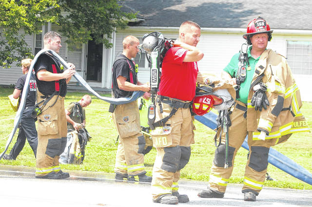 Firefighters pick up their equipment after battling a fire Tuesday afternoon at 1755 Riverside Drive, Sidney. The Sidney, Anna and Van Buren Township Fire Departments responded to the fire along with medics from the Sidney Fire Department, the Sidney Police Department and the Ohio Department of Transportation.