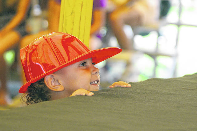 Elijah Owens, 3, of Sidney, looks up at the stage Thursday, July 29, prior to the start of the the Shelby County Fair's Kids Day program. Elijah is the son of Kayla Atkinson.