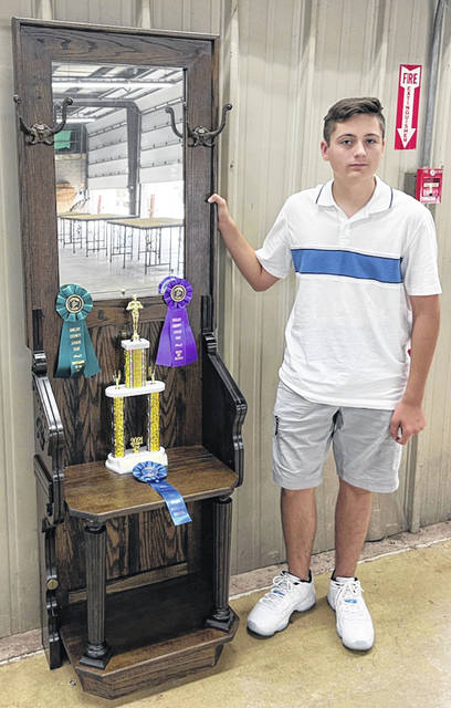 Brady Lumbatis, 14, son of Debbie Lumbatis, won best of class and best of show for woodworking mastery project at the Shelby County Junior Fair. He is also a state qualifier with his project. A member of the Successful 4-H Club, he made his project with Victorian wood that came off of a old organ and the rest was solid oak. The mirror that was put in was made in 1961 and has a copper back to it. The hooks for coat were original Victorian Era as well and the same for the spools that hold up the seat.